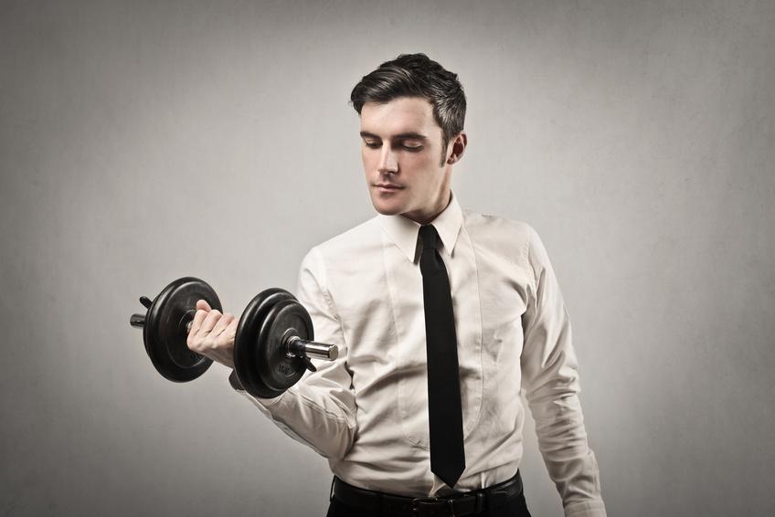 Employé de bureau en chemise, avec une cravate noire qui soulève des poids